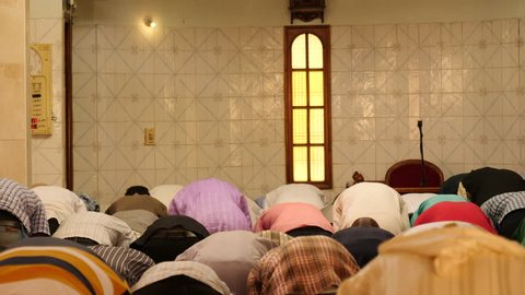 Prayer in mosque, long shot of imam rising.