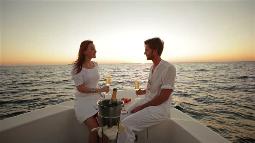 couple drinking champagne on boat at sunset