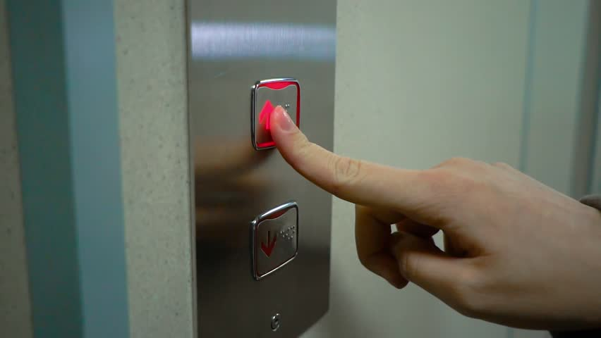 Young Woman Presses a Button of Lift to go Up. Metal elevator. The finger presses the button with the arrow pointed up. Slow motion.