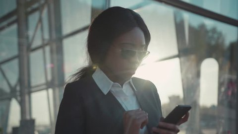 Pretty young Afro-American woman in stylish sunglasses uses her phone, receives bad message, looks disappointed, takes off her sunglasses.