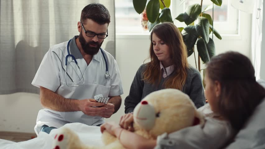 Young sick girl laying on bad and hugging stuffed toy. Doctor giving pills to patient's mother. Three Caucasian people in hospital room. | Shutterstock HD Video #1012721219
