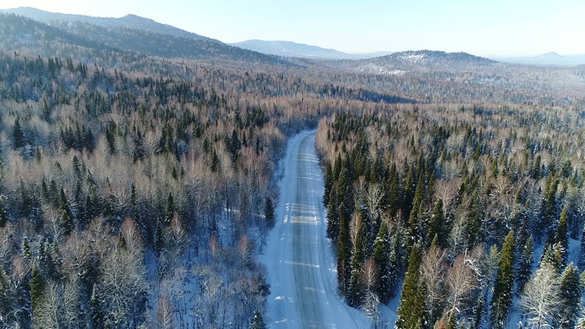 Aerial View. Flight over the Winter Mountain Road. Altai Siberia. Altai is situated in the very center of Asia at the junction of Siberian taiga, steppes of Kazakhstan and semi-deserts of Mongolia
