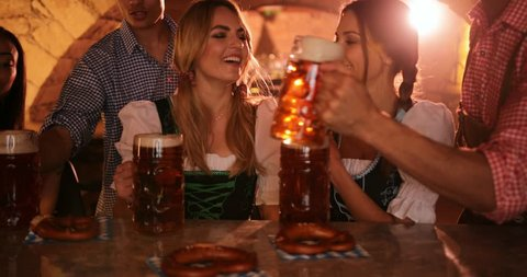 Young multi-ethnic friends drinking beer in beer mugs, toasting and celebrating Oktoberfest in German bar