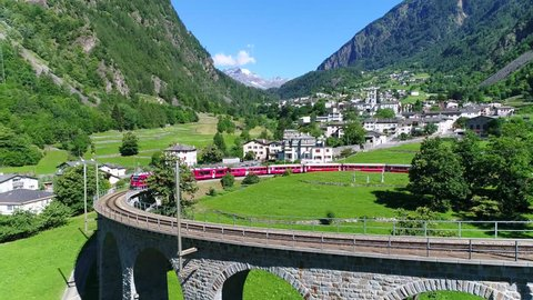Bernina Express, red train of Bernina over the viaduct of Brusio. Unesco world heritage