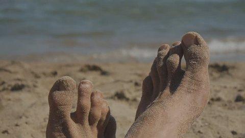 Close-up of feet of caucasian man lying on sandy beach near the sea