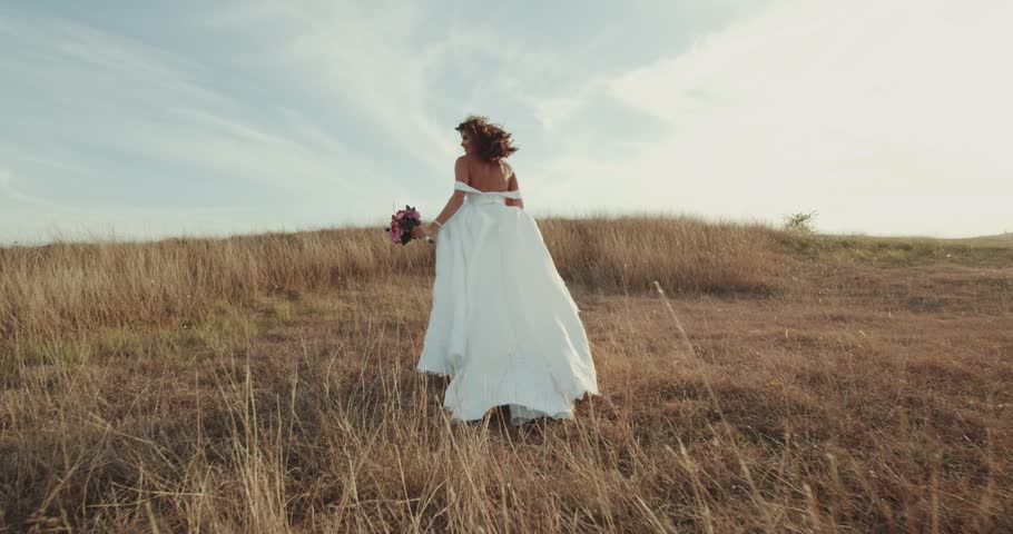 Running bride in amazing long dress through the landscape.