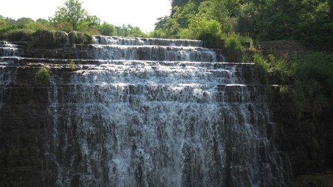 Beautiful half speed slow motion video of Thunder Bay Waterfall with water pouring over the rocky stepped cliff located along a road in Galena Illinois.