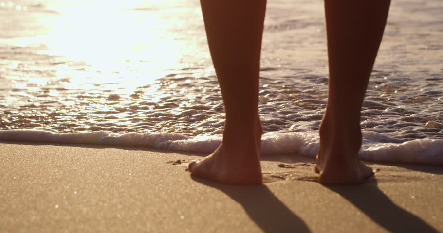 Woman's feet at beach near ocean waves splashing at sunset. Shot with a RED camera. 4k footage.