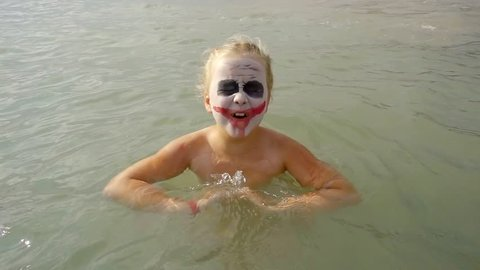 little girl with face art joker style is bathing in sea water and splashing in camera, shouting and grimacing