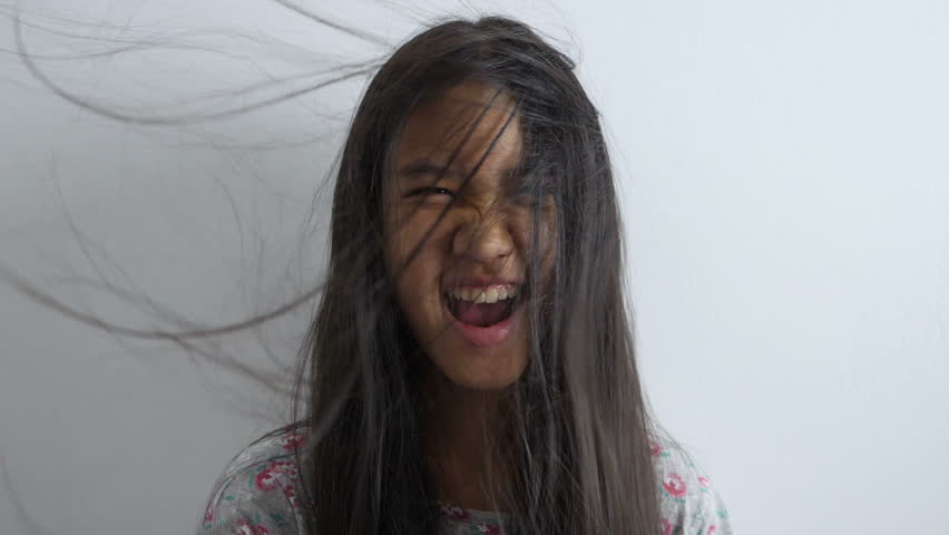 Slow motion shot of Happy Asian girl playing with hair blowing on white background