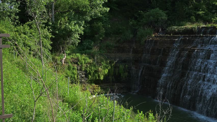 Panning shot of the beautiful Thunder Bay Waterfall with water pouring over the rocky stepped cliff and vibrant green foliage and trees flanking the falls in Galena Illinois.
