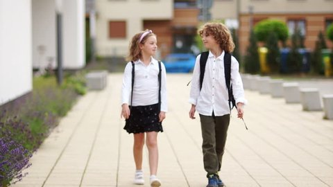 The boy and girl come back from school and talk. Children are dressed in school uniform and are carrying backpacks, school friendship.