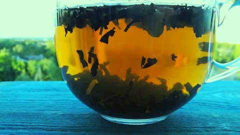 Macro video of pouring boiled water in tea leaves in glass cup. Brewing of black tea. Macro of the process of brewing herbal tea in a glass transparent teapot