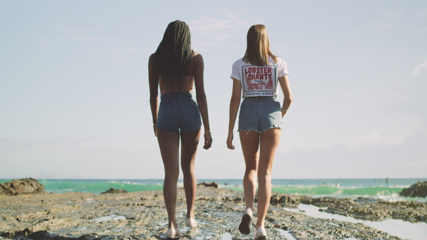 Two best friends walking together along beach near the ocean water. Shot with a RED camera. 4K footage.