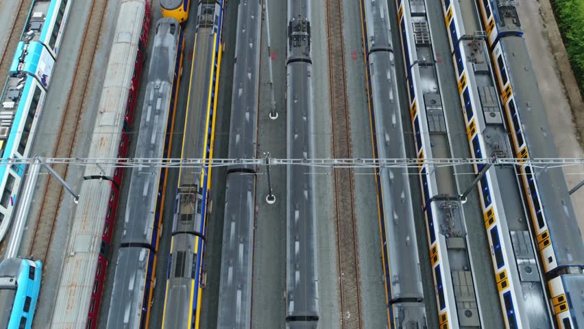 Aerial footage moving backwards over railway hub showing several trains parked next to each other dark grey roofs and colorful train sides in between trains also showing the free railway tracks 4k | Shutterstock HD Video #1012857149