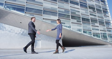 Business Handshake - business people meeting shaking hands. Handshake between business man and woman outdoors by office building. Casual clothing, young people, 30s. shaking hands closeup. SLOW MOTION