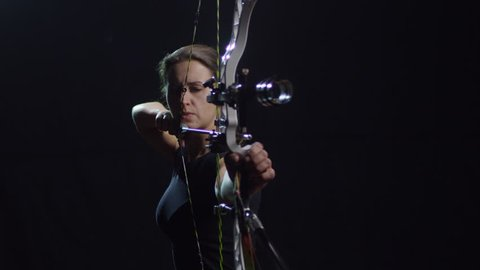 Studio shot of determined female archer with bow shooting arrow against black background