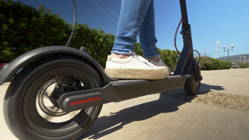 Close up - Female riding electric scooter. Modern transportation gadget and popular futuristic device among young people | Shutterstock HD Video #1012886339