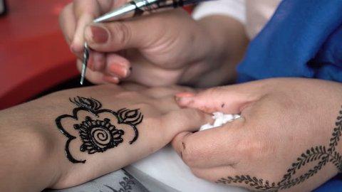 25c9a3df1 Sofia, Bulgaria - 16 June 2018: Woman paints black henna tattoo on a girl's