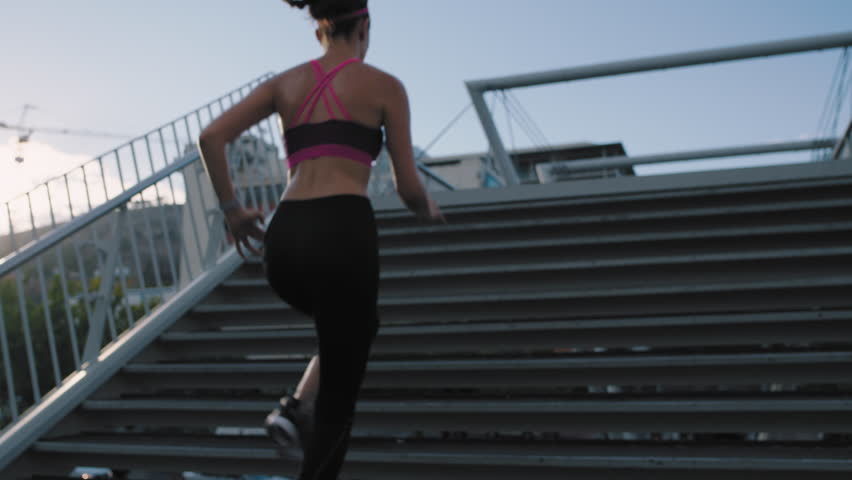 woman athlete legs running up stairs training intense cardio workout exercise female runner feet jogging in urban city background background