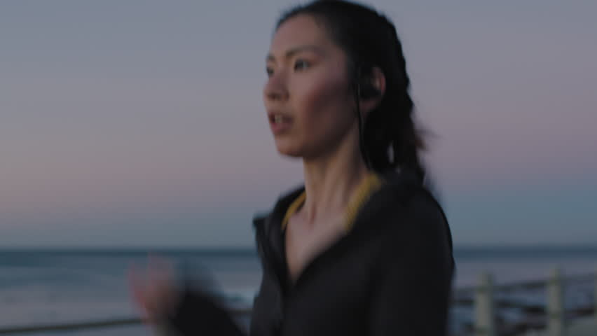 attractive young asian woman running training cardio jogging enjoying fitness workout lifestyle on seaside at sunset