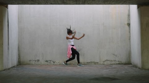 dancing woman young mixed race street dancer performing freestyle hip hop moves enjoying modern dance expression practicing in grungy warehouse