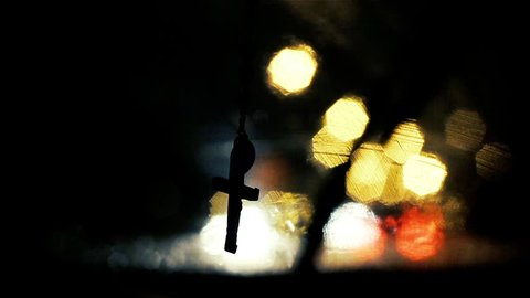 Rosary Hanging from Rear View Mirror of Car at Night,  Blurred Street Lights in the Back.
