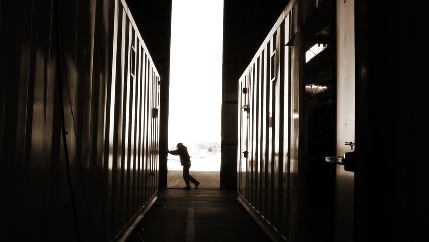 Warehouse Worker Pushing Metal Door. Sepia Tone. Zoom In Shot. | Shutterstock HD Video #1012967039