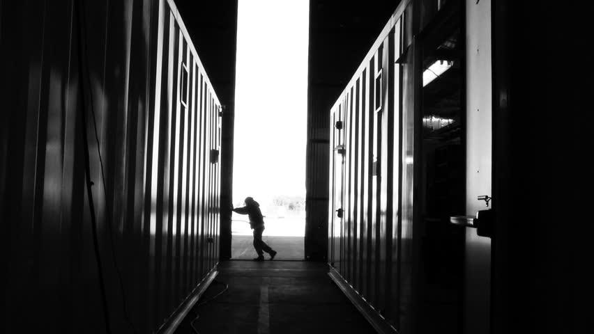Warehouse Worker Pushing Metal Door. Black and White Tone. Zoom In. | Shutterstock HD Video #1012981469