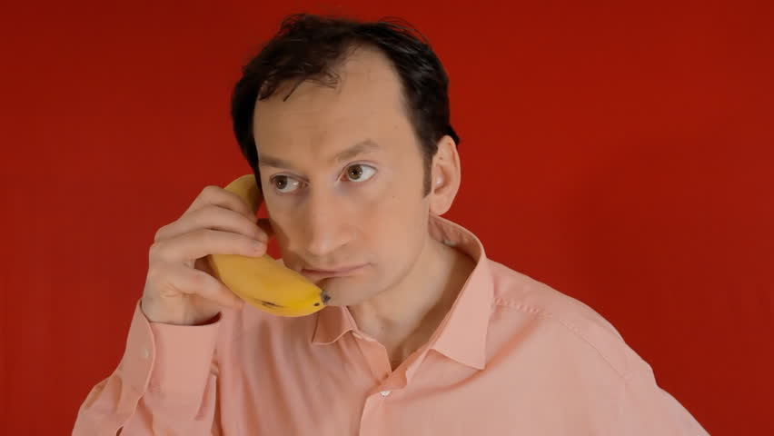 A funny ugly man talking on a banana phone, getting nervous. Red background.  | Shutterstock HD Video #1013009699