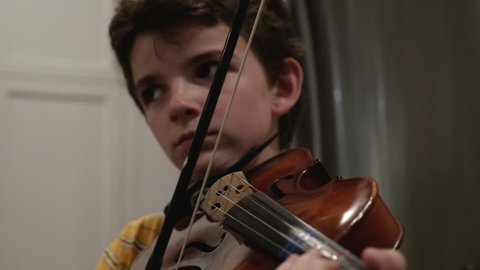 Young male child age 10 - 12 looking away from the camera while playing violin