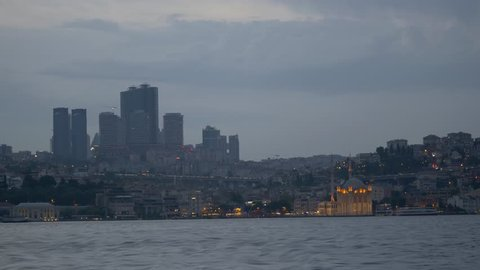High rise buildings and Ortakoy Mosque in Istanbul. Time Lapse. City skyline, showing the buildings rising above Besiktas Region