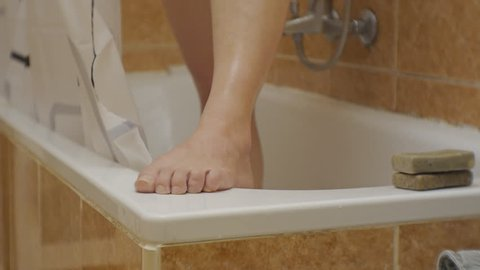 Woman taking a shower. Close-up of female foot standing on the bath's side. Young caucasian woman soaps her sexy legs