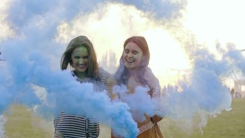 Two young women with smoke bomb celebrating the summer festival