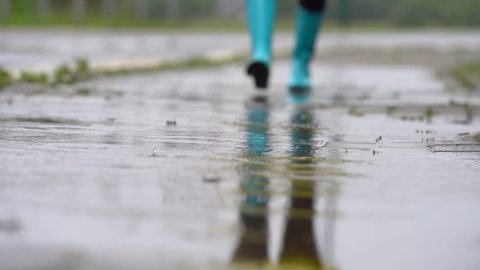 Feeling protected in her boots. Close-up of woman in rubber boots jumping on the puddle. Slow motion