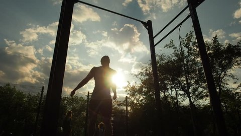 Young Male Athlete Sports Man Training Outdooors Summer Doing Pull Ups Horizontal Bar. Fitness, sport, exercising, training and lifestyle concept - young man doing pull ups on horizontal bar outdoors.