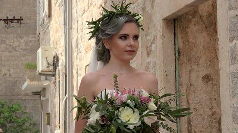 Bride in flower wreath is posing with bouquet. Perast, Montenegro