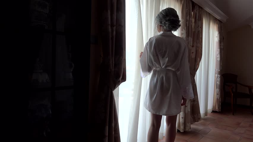 Bride in a white silk dressing gown walks along the panoramic window.