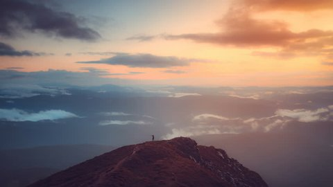 Man stand on top of mountain in sunrise soft light. Majestic nature landscape. Morning fog and clouds floats. Lifestyle, holidays, travel and recreation. Vintage toning. Slow motion 4K Time Lapse