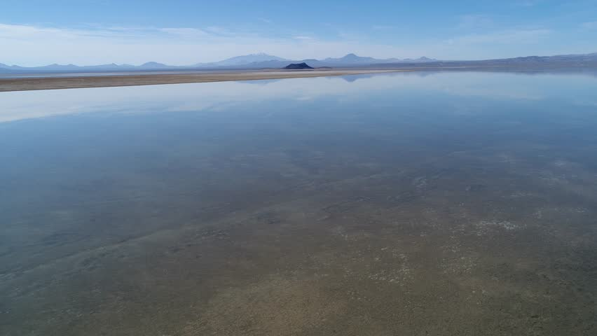 Aerial drone scene of Llancanelo lagoon in Malargüe, Mendoza, Argentina. Water with reflection and white dry salty shore ground. Camera moving forwards towards a volcano. Payunia and Nevado mountains.