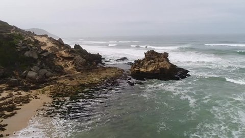 Aerial drone shot flying over dangerous rocky cliffs and out over choppy waves in the ocean in South Africa