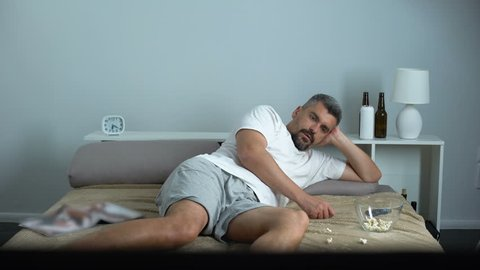 Man falling asleep while eating popcorn in front TV, bachelor passive lifestyle