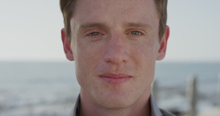close up portrait handsome young red head man laughing happy student enjoying successful lifestyle relaxing on warm summer day seaside slow motion ginger freckles #1013095619