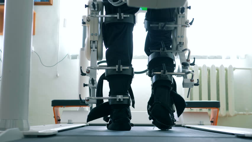 Back view of male legs getting moved by a walking simulation machine. Virtual reality simulator for patient rehab.