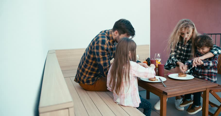 Caring young parents are helping their children to slice the meat during the family dinner.