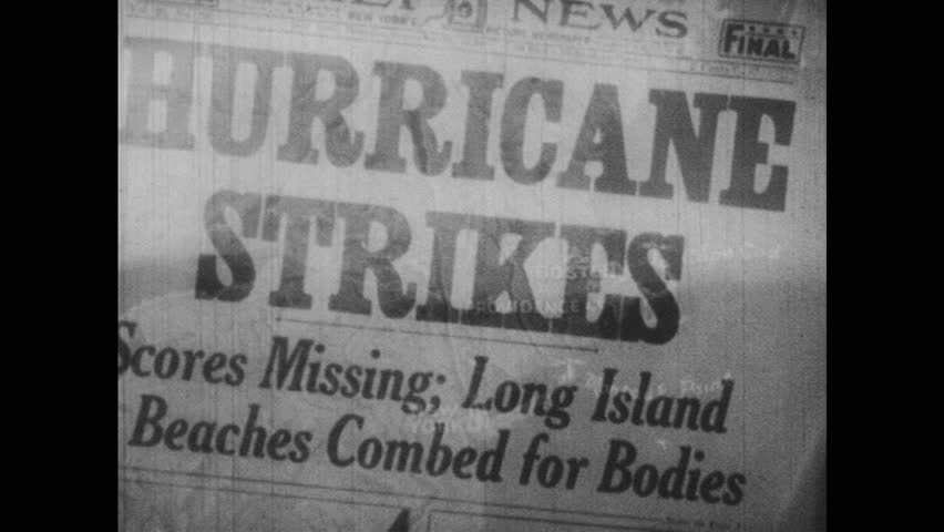 1940s: newspaper headline reads hurricane strikes. giant waves hit beach and wash over house, smash windows and break walls. trolley sits in flood water next to car roofs on city street.