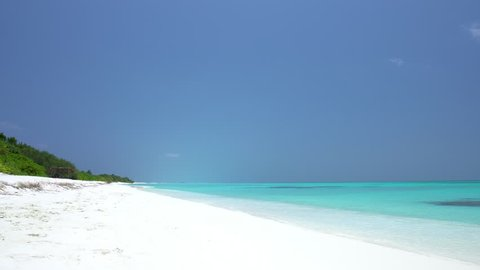 Tropical sandy beach with calm waves. Maldivian destination with nobody