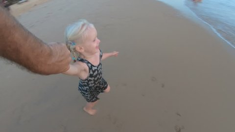 Little baby girl is whirled by father on sandy beach at sunset go pro