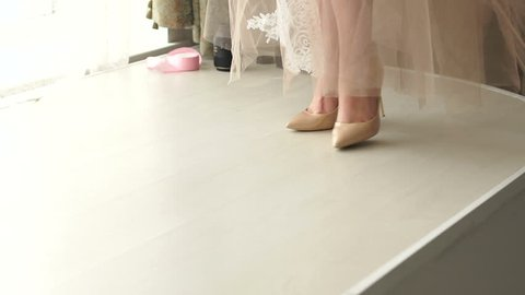 Close-up of a girl in high heels and a long translucent dress is on the catwalk, slow motion. Underwear. The bride in the negligee in the boudoir.