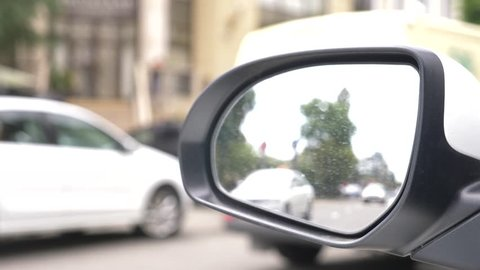 rear view mirror of the car with traces of rain. a blurry reflection in the rear-view mirror of a car standing on the roadside, passing cars and passing pedestrians. 4k, slow motion